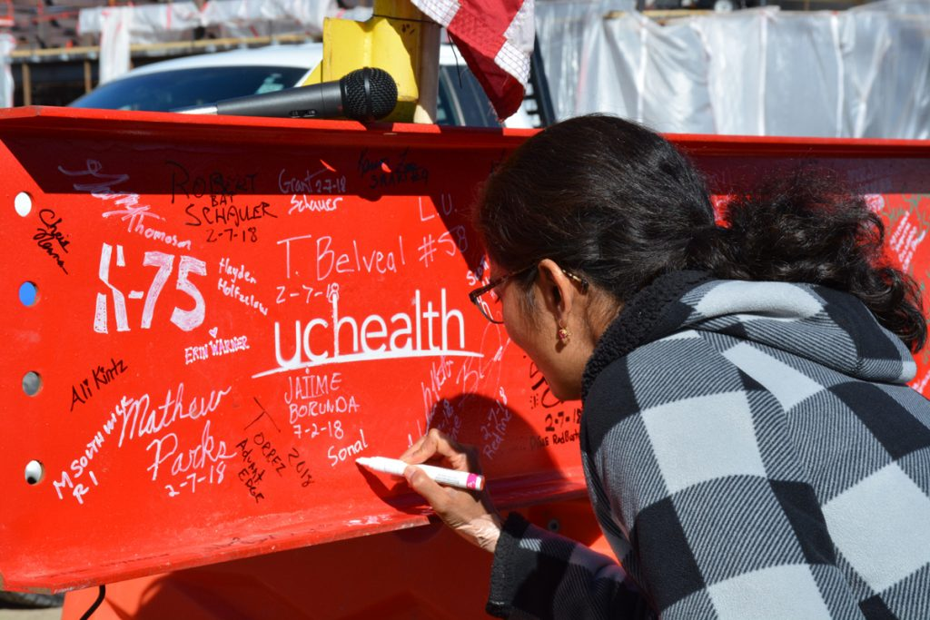A woman signs her name to a beam placed on an expansion of Memorial Hospital North during a 'Topping Off' ceremony on Wednesday.