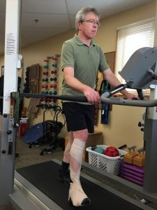 Macpherson doing physical therapy on the treadmill as part of his stroke recovery therapy.
