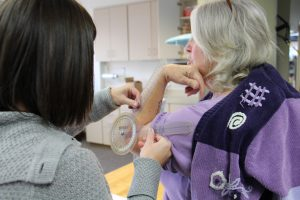 Emily Tjosvold uses a device to measure the flexibility in Barb Wheeler's elbow.
