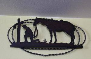 A decorative art piece made of metal, depicting a soldier kneeling at a cross, with his horse nearby.