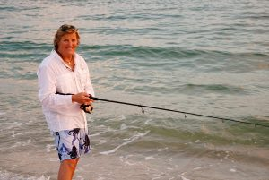 A man with a fishing pole on the beach.