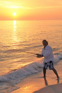As the sun sets, man fishes from a beach.