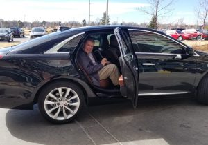 UCHealth patient Jeff Barker sits in the back seat of a car with the door open.