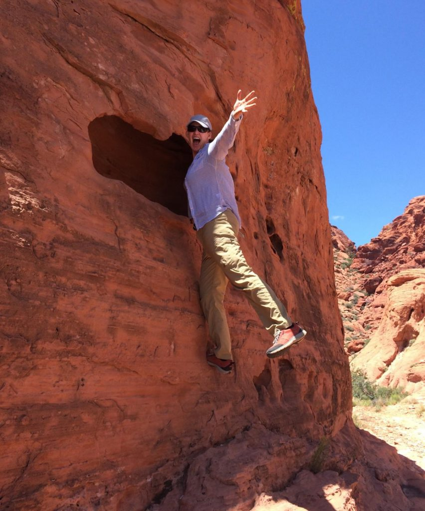 A full life with cancer. Dr. Ali Coffey decided to move to Colorado to live a more beautiful life after learning she had Stage IV lung cancer. Here she climbs a red rock.