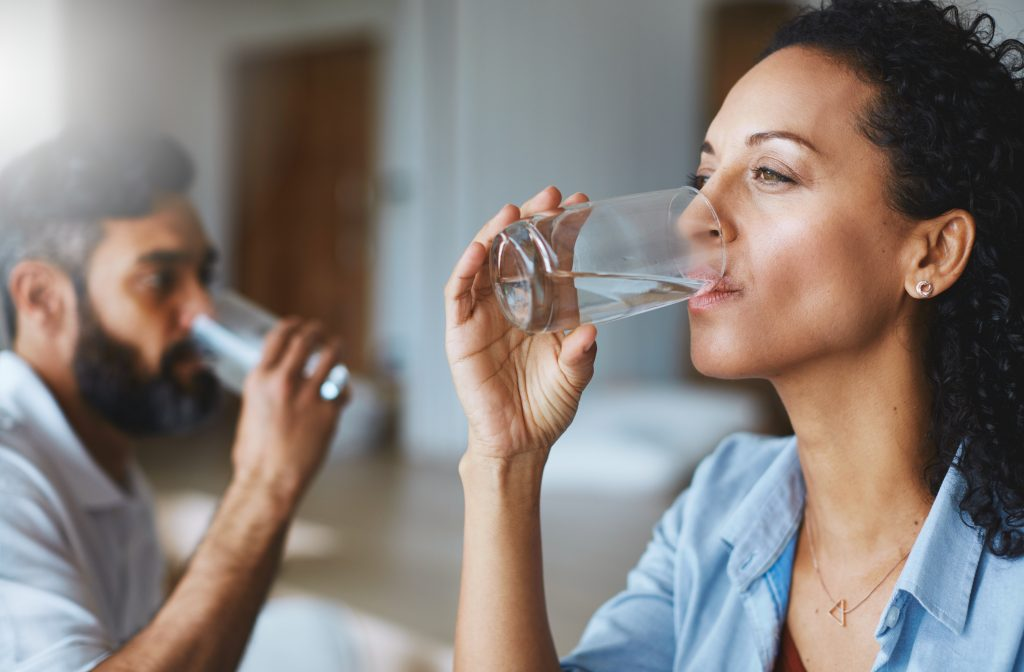 A photo of two people drinking water from glasses.