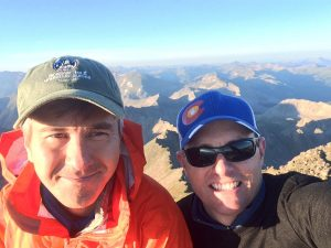 Dr. David Kuwayama, left, with Dr. Robert Meguid. They are smiling in a selfie at the top of a Colorado 14er.