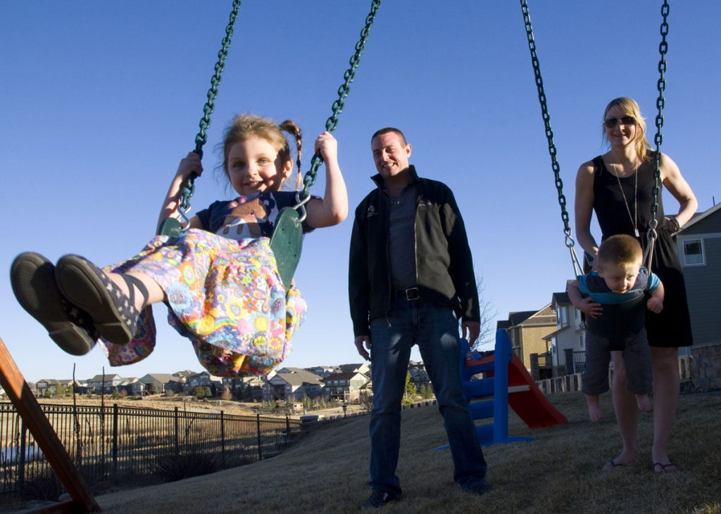 A mom and dad gently push their two children on swings.