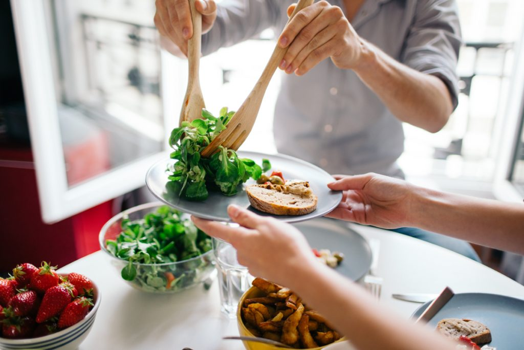 A woman serves up salad on a plate. Americans are getting more and more obese. Downsizing your portions is a quick way to reverse weight gain.