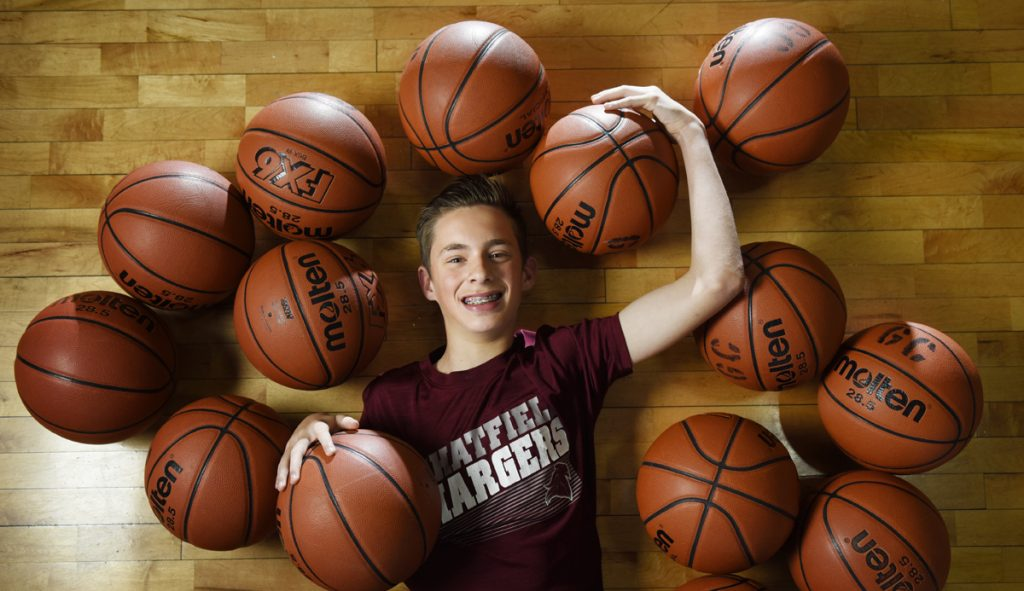 Parker Teff poses surrounded by several basketballs.