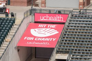 "A red ""Hit the Mitt"" sign at Coors Field in Denver. The sign shows a big mitt with Hit the Mitt spelled out around it and UCHealth at the top. Each time a Rockies player hits a homer that strikes the sign this year, the Gold Crown Foundation will get $5,000."