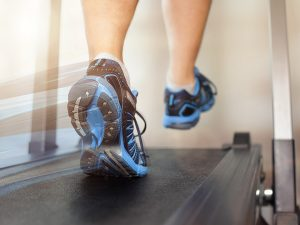 Shot of running shoes on a tread mill as a person runs.
