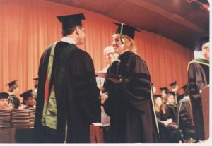 Dr. Jeanne Lewis, wearing a black cap and gown, receives her diploma on a stage at her medical school graduation.