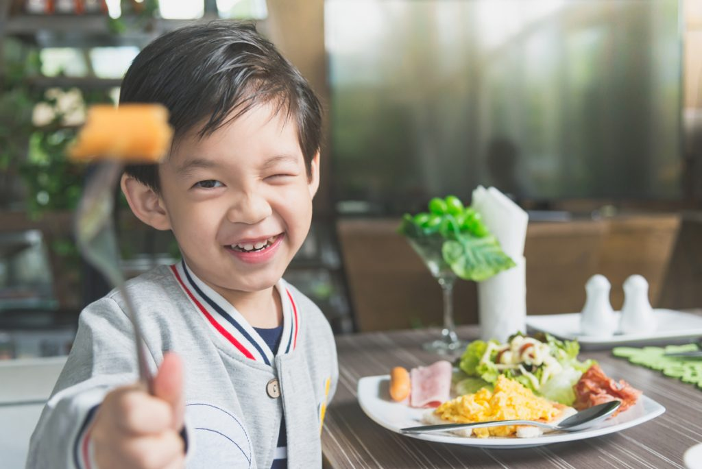 A Kid Eating Breakfast In Restaurant