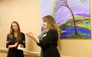 "Anna Smoot, PVH and MCR Foundation development officer, right, introduces artist Tanielle Childres, left, and her painting, ""What a Wonderful World,"" at a recent event at UCHealth Medical Center of the Rockies. It's one of two paintings she's donated to UCHealth since losing her unborn child in 2012, and again in 2016."