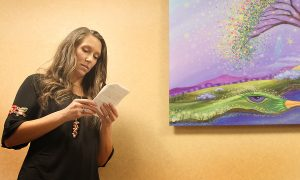 "Artist Tanielle Childres explains what her painting, ""What a Wonderful World,"" symbolizes. The painting, which is created and donated to UCHealth Medical Center of the Rockies after her mischarge, now hangs in the hall of the Women and Family Unit."