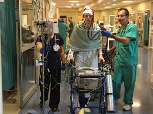 A photo of a man walking in the hospital with caregivers and life-saving medical devices nearby.