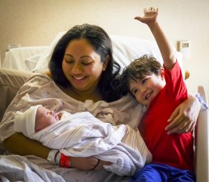 A mother, in the hospital bed, introduces her new-born son to her three-year-old son when the new-born son is only hours old. The three -year-old is ecstatic to have a new baby brother.