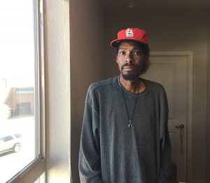 Once homeless, Julian Jones now has a medical home and an apartment too. Here he poses near a window in his new apartment. He's very tall and is wearing a baseball cap.