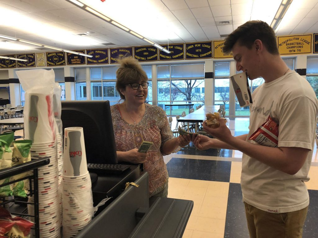 Vicki Burke stands at a cash register and collects money from a customer at Holy Family High School cafeteria.