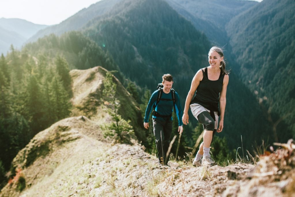 A fit man and woman in their 50's hiking the trail on a mountain ridge, a beautiful river gorge spreads out behind them. They smile, enjoying the exercise, the beauty of nature, and staying strong.