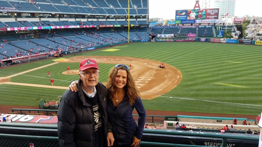 Louisa Drouet poses with her dad. They're at a baseball game in Los Angeles. Drouet lost her dad a year ago. She's been coping with breast cancer since his death.