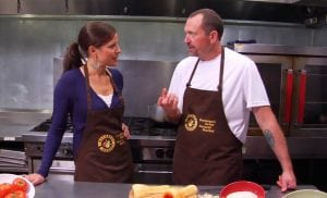 Louisa Drouet was a broadcaster for many years. Here she does a cooking segment. She's wearing an apron and interviewing a chef.