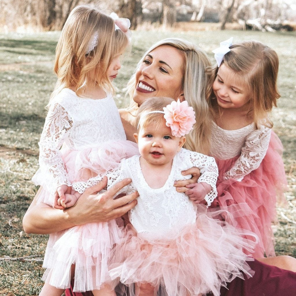 mom holds her three young daughters all in two-twos.