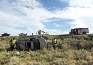 This photo shows the accident scene after Doug Zirkle's crash. His champagne-colored Jeep lays smashed on its side about 30 feet down an embankment outside Craig, CO. There are emergency vehicles up the hill and the sky is blue.