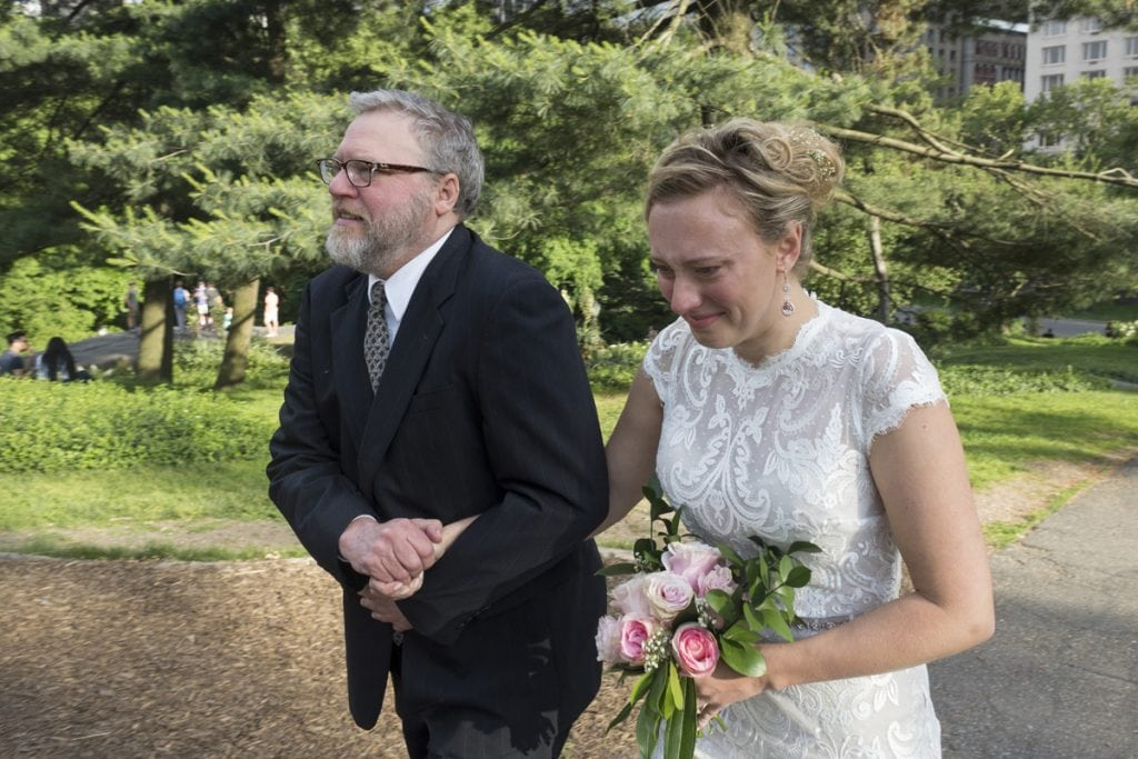 Doug Zirkle and his oldest daughter, Rachel, hold hands on Saturday as he walks her down the aisle, but really up a path, at her wedding in New York City's Central Park.