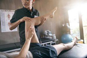photo of physical therapist working on patient's knee