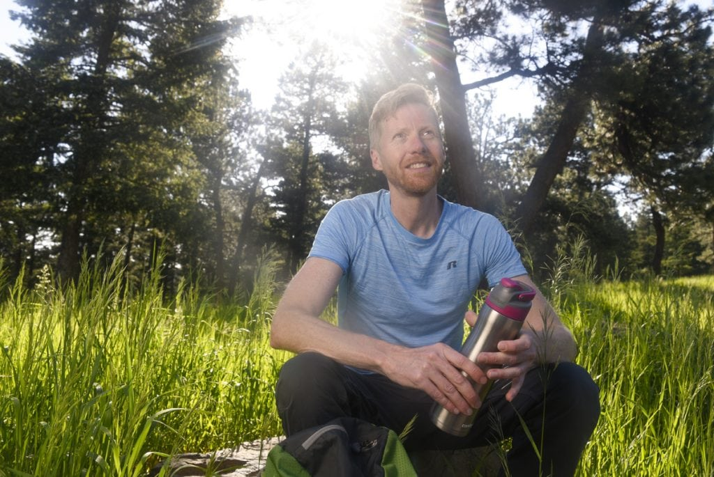 Jonathan Proctor, an environmentalist and former wilderness ranger, sits on a rock in the forest. The sun is bright behind him. He was born with a condition called pectus excavatum. His breast fone was pressing in on his heart and causing shortness of breath.