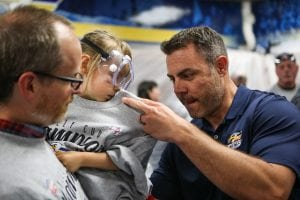 A Colorado Eagles coach autographs a fan's tshirt at a special locker room celebration for UCHealth cancer survivors.