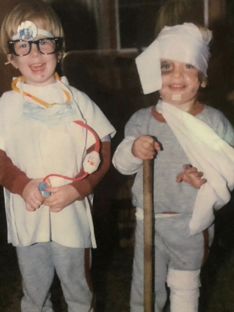 This photo shows two boys who are about 5 or 6. They are twins and are dressed up for Halloween. One is dressed as a doctor and the other is his patient.