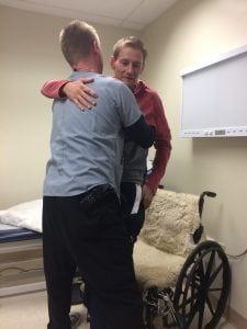 Archie hugs his physical therapist and rises from his wheel chair for the first time. The moment gave him hope that he would ride, rope and ranch again after a terrible head-on car crash.