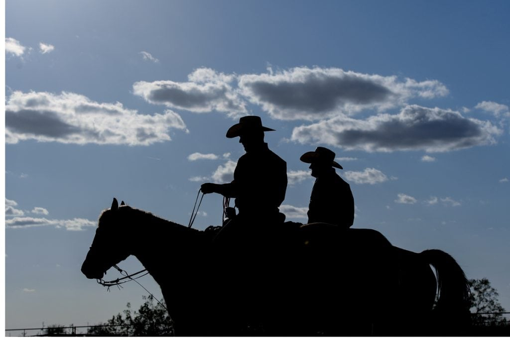 A silhouette shows two men on horseback together.