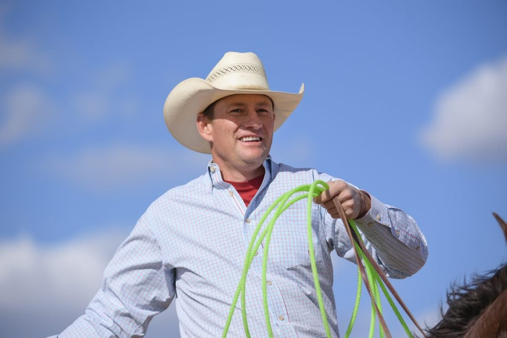 Archie Chant holds his green rope as he sits on his horse. He's wearing a cowboy hat. Thanks to the help he got after a terrible car accident, Archie is riding, roping and ranching again.