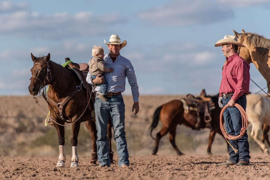 Archie Chant holds his son, Hudson. Next to him is his doctor, Jason Stoneback. Their horses are behind them.