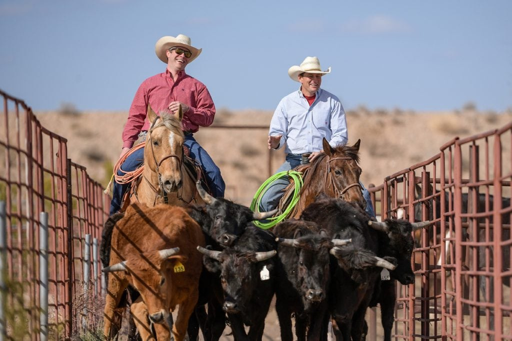 Dr. Jason Stoneback, left, is on his horse riding through a corral next to his patient, Archie Chant, who is also on his horse. They're riding side-by-side.