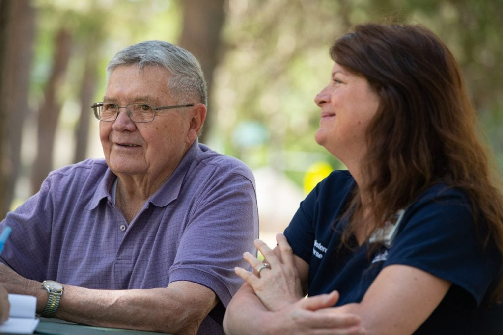 A cancer patient chats with his nurse navigator while sitting at a picnic table in a park.