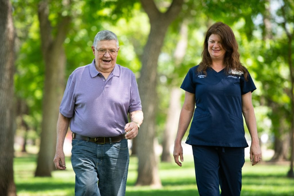 a man walks in a park with his nurse navigator outside UCHealth Memorial Hospital.