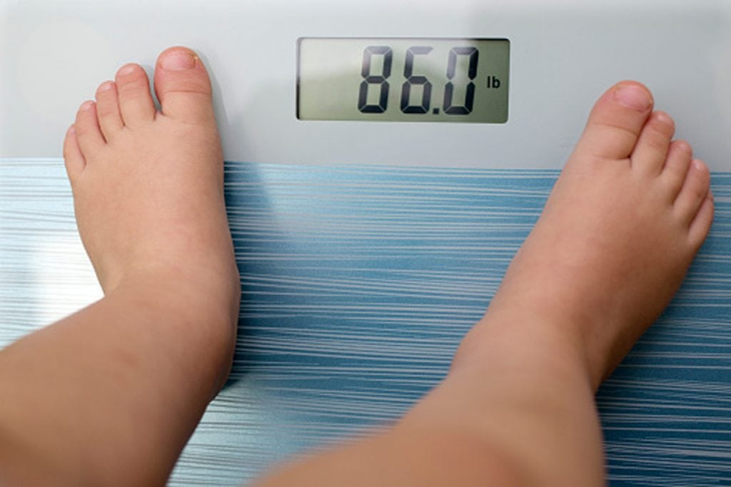 an overweight child steps on scale