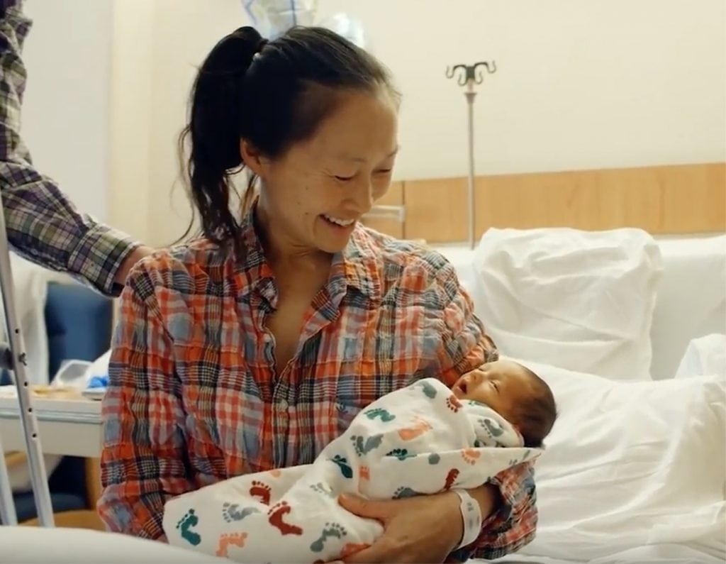 A mother wearing a flannel shirt gazes down at her newborn, who is wrapped in a blanket.