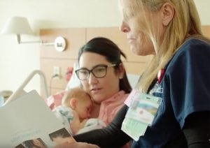 A nurse shows a mom a breastfeeding booklet as she holds her baby close to her chest.