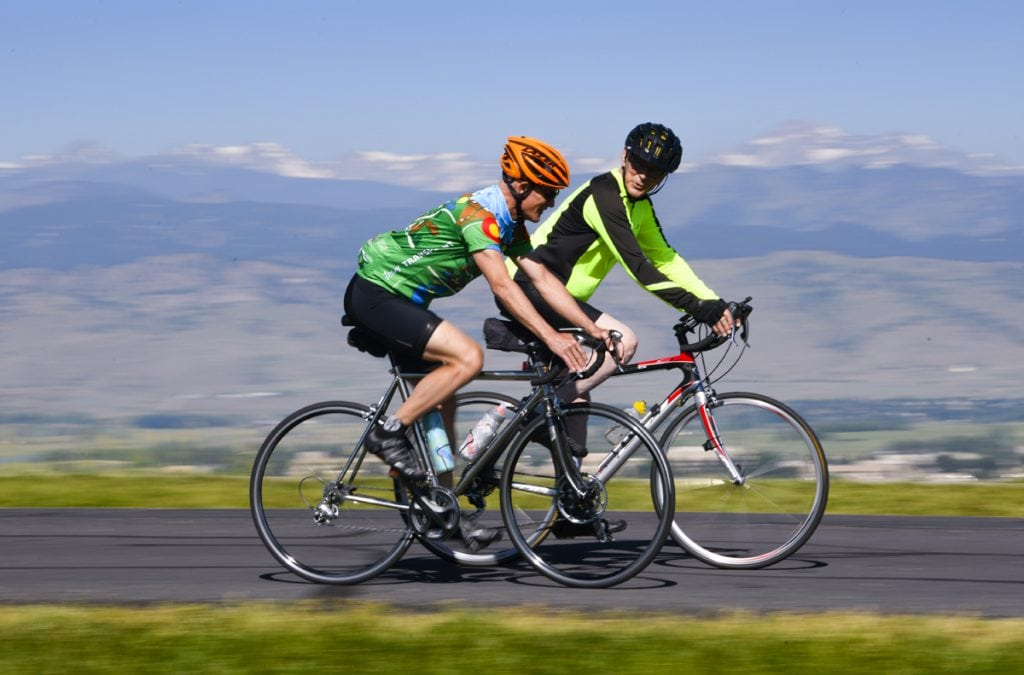 Scott La Point and Jim Eastman cycle together on a road with mountains in the background. They are near Niwot, CO. The men both survived traumatic brain injury, then La Point donated his kidney to Eastman. The men will be cycling in the Transplant Games of America.