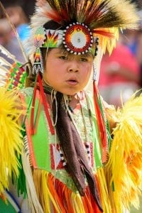 A boy in yellow Indian garb and a headdress dances during festivities at Cheyenne Frontier Days.