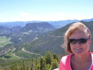 Trisha Washburn poses at the top of a mountain with a view behind her. She's coping with Alzheimer's and anxiety and is getting help through integrated care at her primary care clinic.