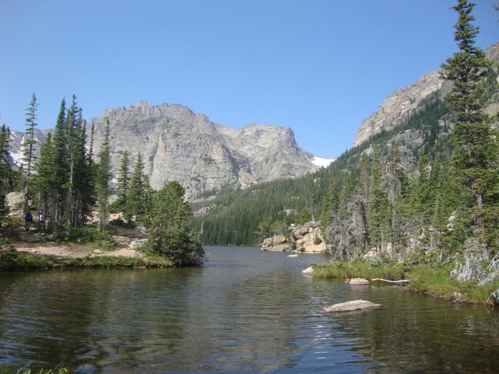 A photo of an alpine lake in Rocky Mountain National Park called The Loch. In the foreground, you see the lake and behind it are some pine trees and mountains.