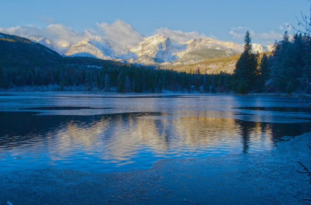A photo from Rocky Mountain National Park. It shows a lake in the foreground that is beginning to ice up in November and snow-dusted peaks in the distance.
