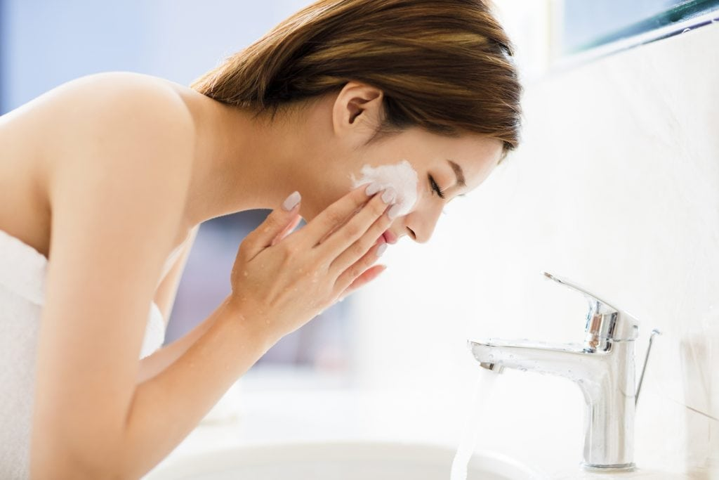 A young woman is show washing her face.