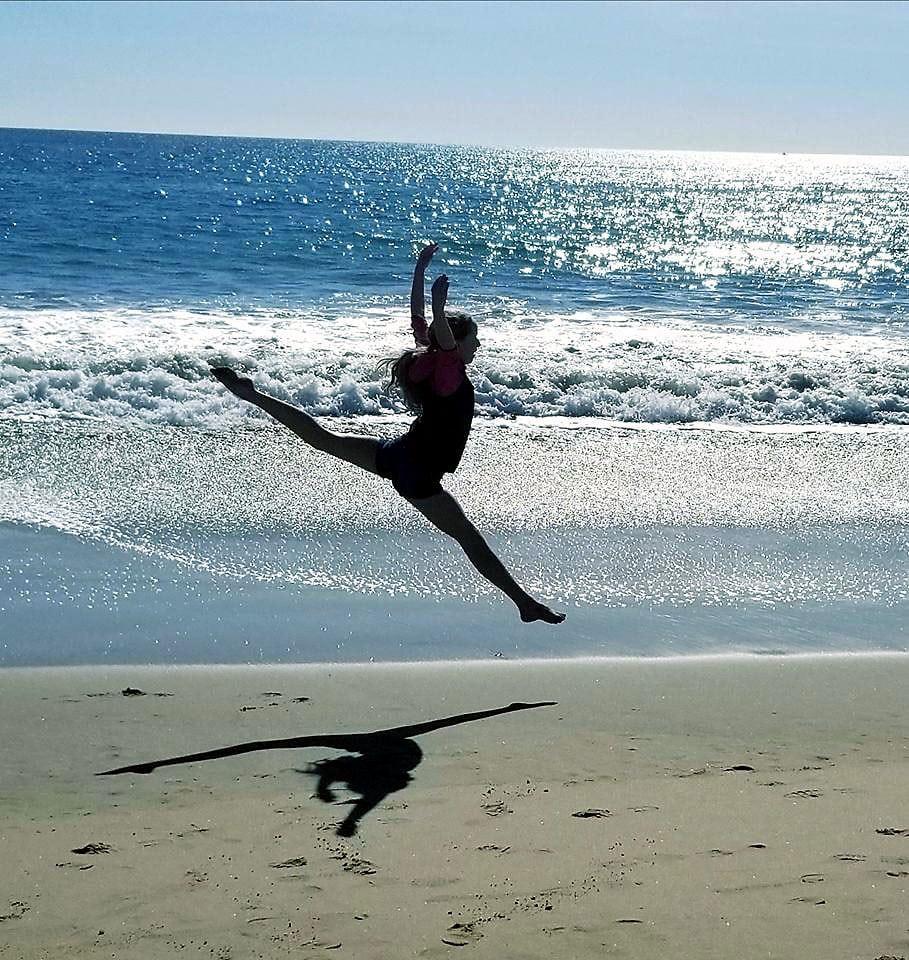 Amelia leaps through the air on a beach.